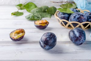 Fresh picked plums in a wicker vase