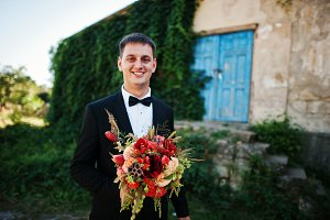 Portrait of a handsome groom holding