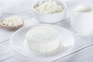 fresh cottage cheese, wooden spoon a