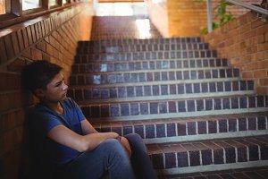 Sad schoolboy sitting alone on stair
