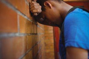 Sad schoolboy leaning on brick wall