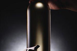 cropped shot of man holding bottle o