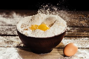yolks falling into bowl with flour o