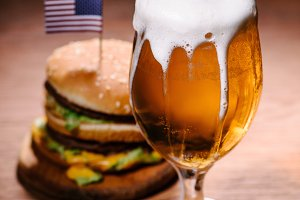 tasty burger with glass of beer on w