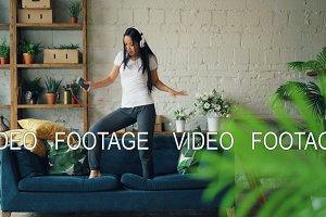 Cute Asian girl is dancing on sofa
