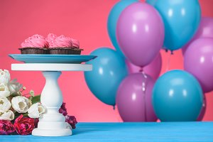 pink cupcakes on cake stand and bouq