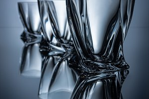 row of three cognac glasses on grey