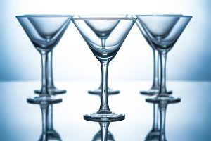 row of empty martini glasses on grey