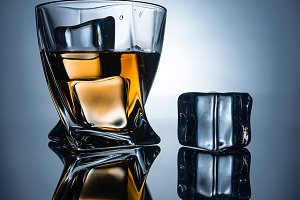 glass with cognac and ice cubes with
