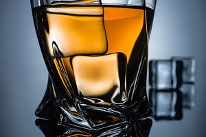 glass of whiskey with ice cubes with