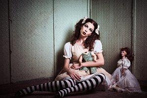 Strange sad girl with dolls