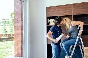 Couple kissing while unpacking boxes