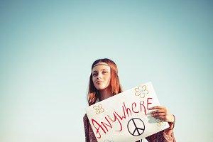 Beautiful hippie girl hitchhiking