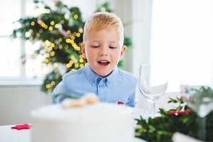 A small boy looking at a cake at