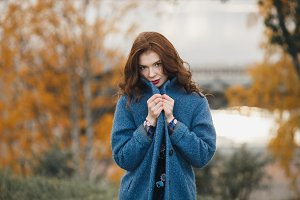 Trendy young woman in warm blue coat