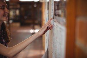 Schoolgirl looking at notice board