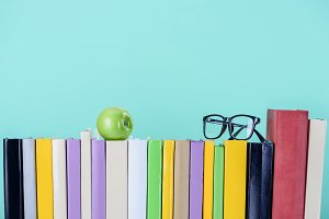 row of books with apple and glasses