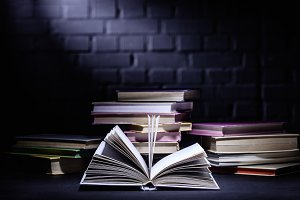 open book in front of stack of books