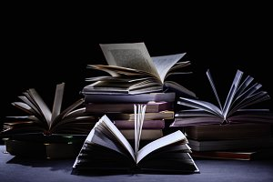 stack of books on dark surface on bl