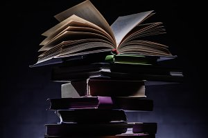 stack of books with open book on top