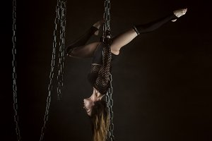 Woman gymnast is hanging on chains.