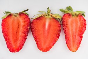 Three halves of strawberries on whit