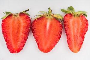 Three halves of strawberries on whit