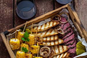 Box loaded with pastrami and corn
