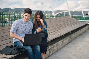 Couple using and looking a laptop
