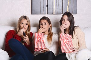 Three young friends eating popcorn a