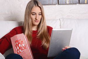 Young woman eating popcorn and watch