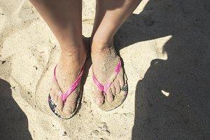 Woman feet with flip flops on the sa