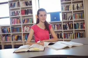 Schoolgirl doing homework in library