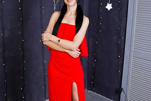 Brunette girl in red dress posed nea