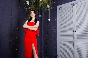 Brunette girl in red dress posed nea