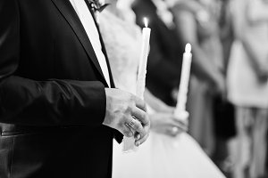 Newly married couple holding candles