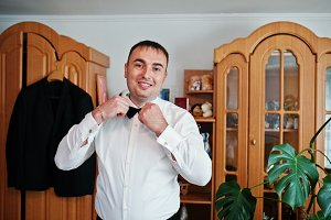 Handsome groom dressing up in his ro