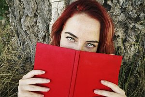 Young woman reading a red book