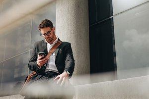 Entrepreneur sitting outdoors typing