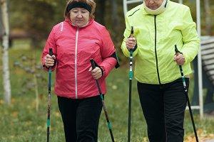 Old women in jackets walking on