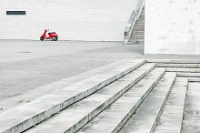 Red scooter against white wall by  in Transportation