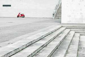 Red scooter against white wall