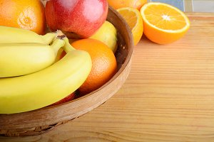 Basket of fruits on wooden table.