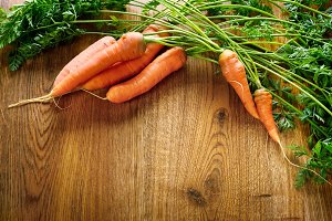 Fresh carrots on wooden table in kit