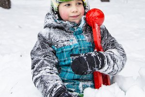 child boy playing in the snow in