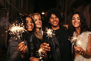 Four young friends with sparklers