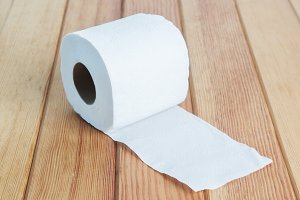 White toilet tissue roll on wood