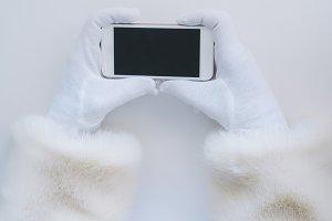Santa Claus hands holding a smartpho