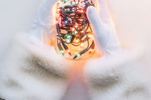The hands of Santa Claus holding a g