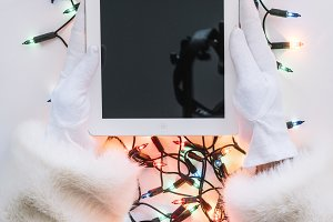 Santa Claus hands holding a tablet w